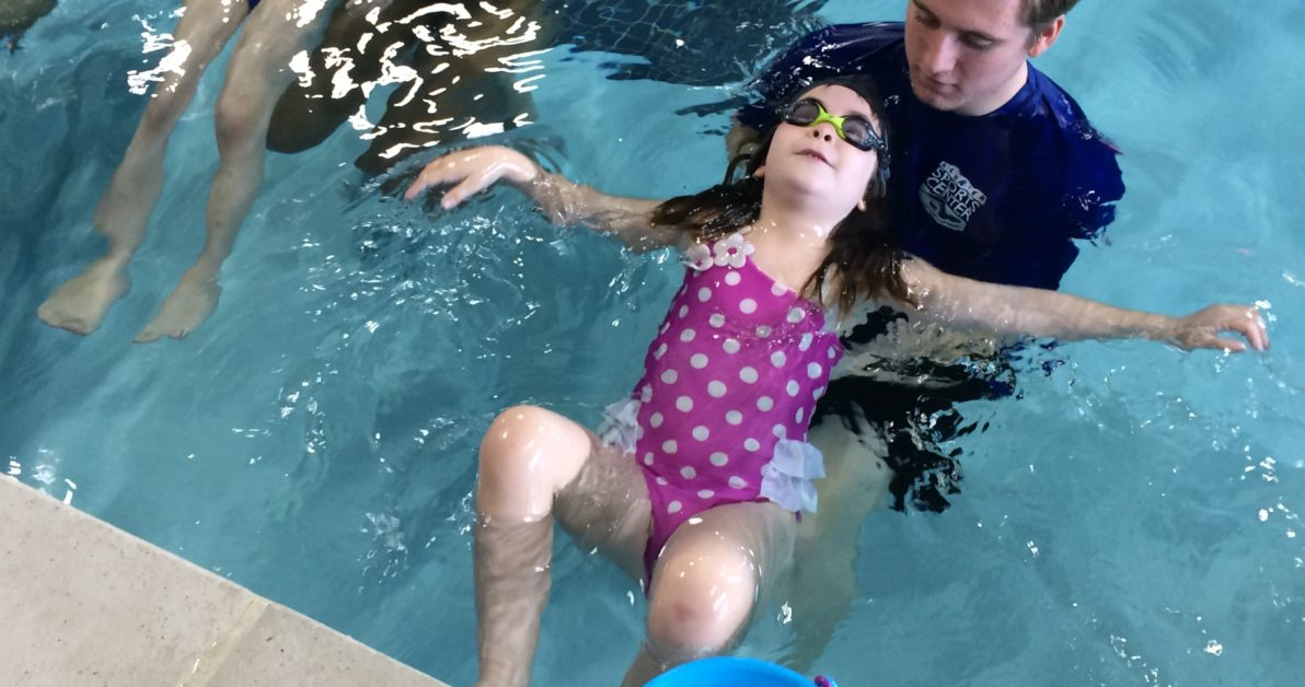 young girl floating on back with swim instructor during aquatic physical therapy at Schafer Sports Center