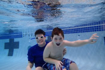 smiling boy underwater in pool at Schafer Sports Center with instructor for special needs swimming lesson