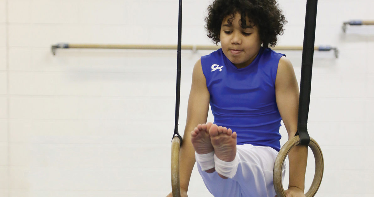 young boy on gymnastics rings at Schafer Sports Center