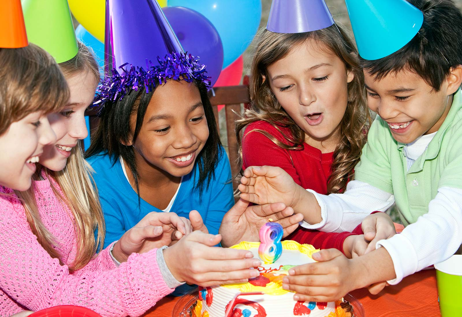 girl blowing out candles during 8th birthday party at Schafer Sports Center
