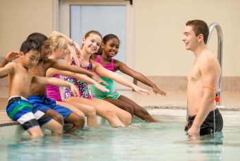 Swim instructor teaching young children swim strokes at Schafer Sports Center